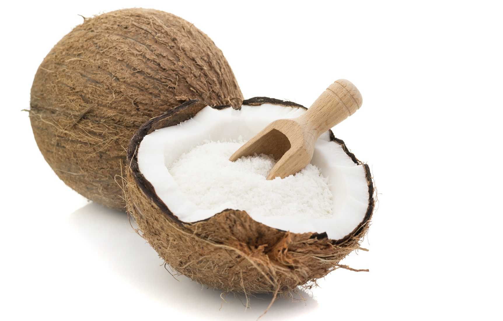 A coconut with desiccated coconut and scoop on white background