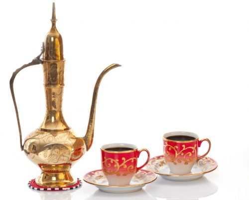 Brass arabic coffee pot with two cups of coffee symbolising hospitality and welcoming guests.